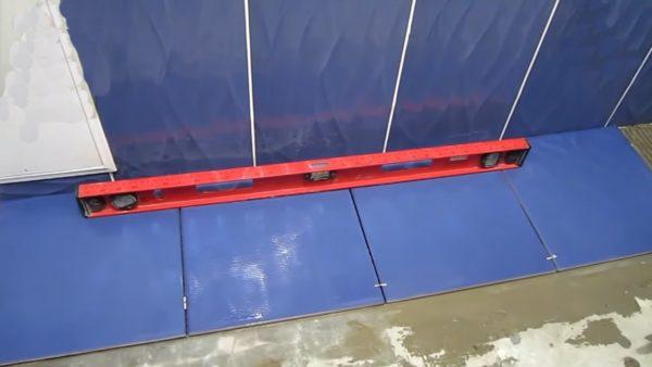 Контролируем ровность укладки плитки строительным уровнем